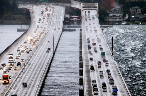 Eastbound traffic lanes, right, on Interstate 90 are dampened by wind-driven waves from the south as the floating bridge calms Lake Washington to the north, left, Tuesday, Nov. 17, 2015, in Seattle. Rain and high winds snarled the morning commute in the Puget Sound area and the Inland Northwest braced for severe weather that could include wind gusts to 70 mph. The National Weather Service says a Pacific storm system arriving Tuesday may include sustained winds of 45 mph that could topple trees and cause power outages. (AP Photo/Elaine Thompson)